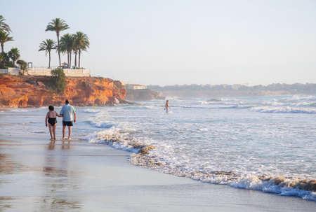 Retired couple on a morning walk on La Zenia beach on July 24 2012. La Zenia, Orihuela, Spain.