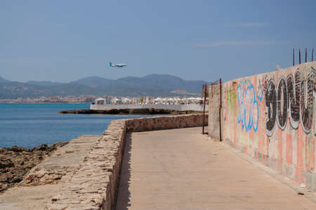trashy: Potential for new development glimpse behind the scenes of Cala Estancia, Majorca. Luxurious day spa Puro Beach and Palma bay in the background. Mallorca, Balearic islands, Spain.