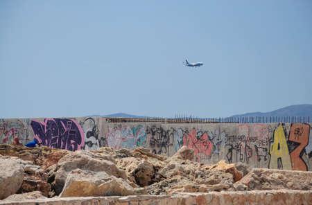 trashy: Ryanair jetliner approaching airport and graffiti in Cala Estancia. Mallorca, Balearic islands, Spain. Editorial