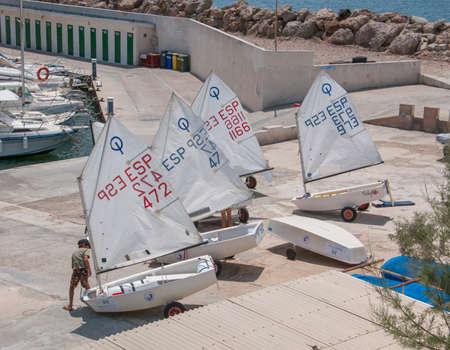 CALA GAMBA, Mallorca, Spanje op 21 juli 2012: Jonge jongen voorbereiding van zijn vrolijke boot op 21 juli 2012 in de kleine jachthaven van Cala Gamba, Mallorca, Balearen, Spanje.