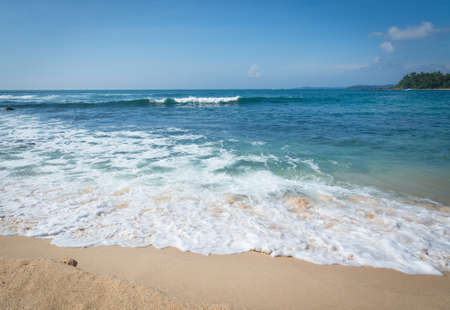 southern indian: Sandy paradise beach with golden sand and emerald green water on the edge of Indian Ocean, Southern Province, Sri Lanka, Asia. Stock Photo