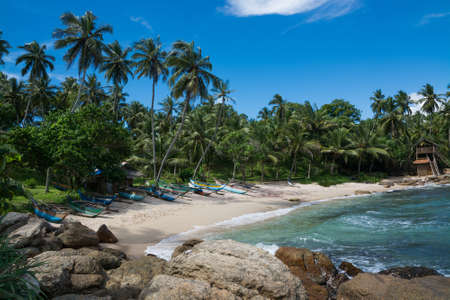 rocky point: Tropical spiaggia rocciosa con palme da cocco, spiaggia di sabbia e barche da pesca tradizionali. Rocky Point, Tangalle, Southern Province, Sri Lanka, Asia. Editoriali