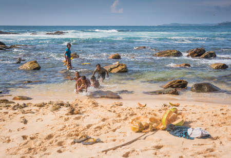 southern sri lanka: TANGALLE, SOUTHERN PROVINCE, SRI LANKA - DECEMBER 16, 2014: Sinhalese woman, boys and girl washing coconuts in the warm water on paradise beach on December 16 2014, in Tangalle, Sri Lanka.