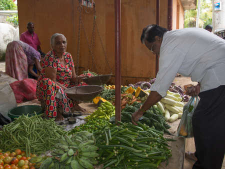 tangalle: TANGALLE, SOUTHERN PROVINCE, SRI LANKA - DECEMBER 17, 2014: Vegetable vendor in the market on December 17, 2014 in Tangalle, Southern Province, Sri Lanka, Asia.