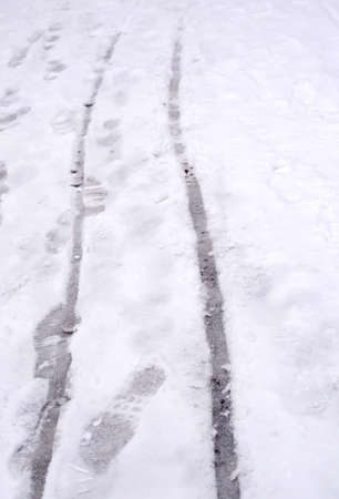 slushy: Baby carriage snow tracks and foot prints in slushy snow in Vallingby, Stockholm, Sweden in January.