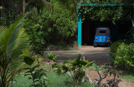 tuk tuk: Blue tuk tuk vehicle parked in lush tropical garden. Southern province, Sri Lanka, Asia.