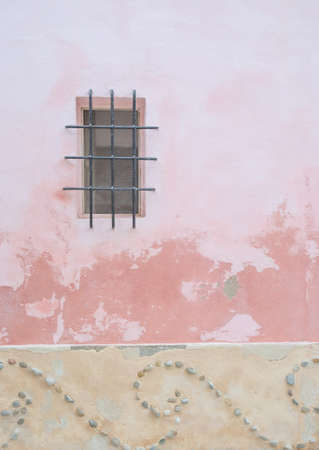 yellow ochre: Pink house with black iron window and decorative friese with little pebbles in yellow ochre.
