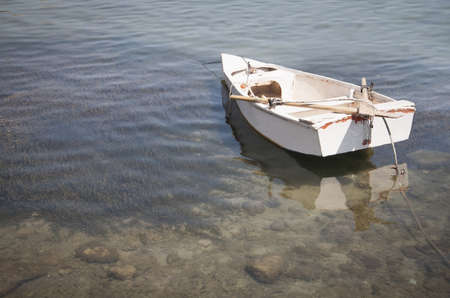 Old white row boat moored on peaceful shallow and transparent water. photo