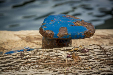 fishnet: Blue Mooring Knob Close-up with rust and flaky paint with fishnet on a jetty, Mallorca, Balearic islands, Spain.