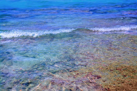 foaming: Deep blue and transparent water with small wave softly foaming ashore.