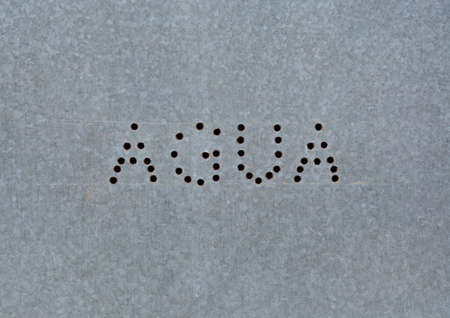 Perforated letters on zink AGUA