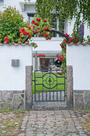 white washed: AHUS, SOUTH SWEDEN - JUNE 28, 2014: Pretty home entrance with white washed wall and roses on June 28, 2013 in Ahus, South Sweden. Editorial