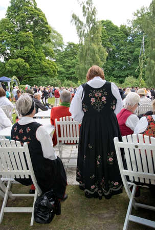 midsummer pole: ALSTER, KARLSTAD, SWEDEN - JUNE 20, 2014: People at Midsummer celebrations and Norwegian - Swedish wedding on June 20, 2014 in Alster, Karlstad, Sweden.