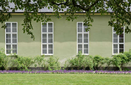 neoclassical: Green neoclassical building exterior tight closeup with lavender flowerbeds and tree foliage. Stockholm, Sweden. Stock Photo