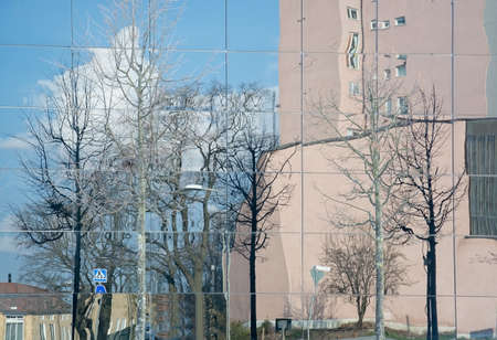 functionalism: VALLINGBY, STOCKHOLM, SWEDEN - APRIL 18, 2014: Abstract architecture. Buildings and trees reflected in modern glass facade on April 18, 2014 in Vallingby, Stockholm, Sweden.