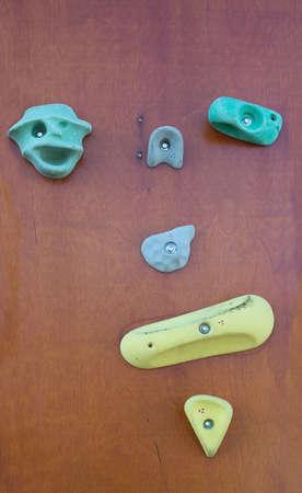 manmade: Manmade rock climbing wall with colorful knobs outdoors closeup. Stock Photo