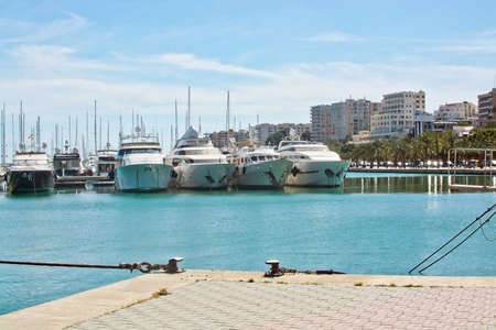 paseo: PALMA DE MALLORCA SPAIN  APRIL 19 2015: Large white expensive motor yachts moored in harbor by Paseo Maritimo with parked cars on April 19 2015 in Palma de Mallorca Balearic islands Spain.