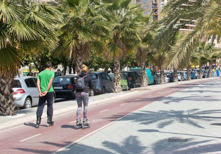 rollerblades: PALMA DE MALLORCA, SPAIN - APRIL 21, 2015: Young couple going on rollerblades along the bike track on April 21, 2015 in Palma de Mallorca, Balearic islands, Spain.