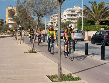 bicyclists: CAN PASTILLA, MALLORCA, SPAIN - APRIL 22, 2015: Bicyclists practice along the track running from Palma all the way to Arenal, on a sunny spring day on April 22, 2015 in Cala Estancia, Mallorca, Balearic islands, Spain.