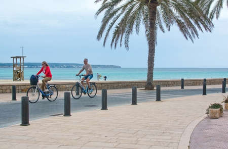 ocea: CAN PASTILLA, MALLORCA, SPAIN - APRIL 22, 2015: Bike track along Can Pastilla with palm trees and beautiful ocean view with horizon on a sunny spring day on April 22, 2015 in Can Pastilla, Mallorca, Balearic islands, Spain.