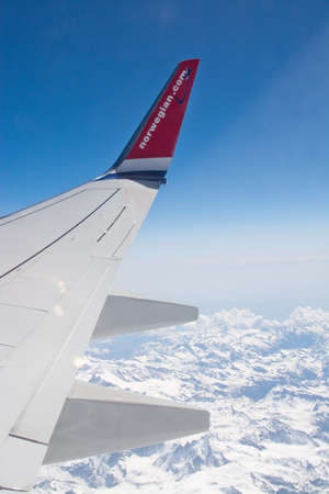 jetplane: AIRBORNE, ALPES, FRANCE - APRIL 24, 2015: Norwegian airliner wing and the snow clad French Alpes below on April 24, 2015 in the air, French Alpes, France.