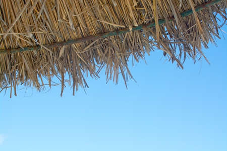 springbreak: Detail of straw parasol and blue sky copy space. Mallorca, Balearic islands, Spain.