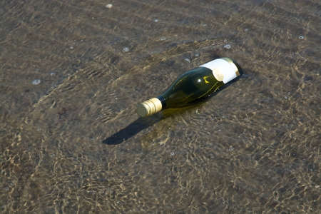 desperation: Stranded bottle with mail on sandy dark beach.