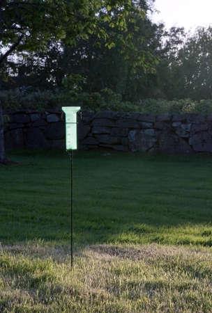 rain gauge: Pluvi�metro verde de pl�stico en el jard�n soleado.