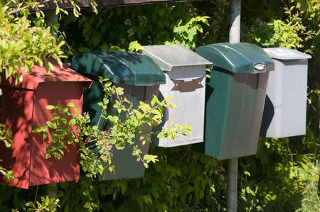 mailboxes: Mailboxes made of plastic in green white and red in a row outdoors in sunshine.