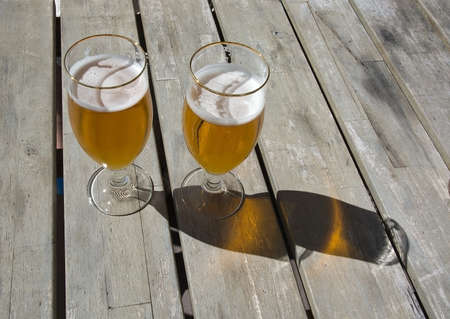 quenching: Two beers on rustic wooden table outdoors in sunshine. Stock Photo