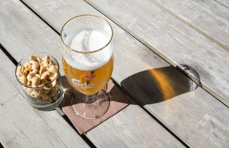 carlsberg: FALKENBERG SWEDEN  JUNE 5 2015: Two beers in Carlsberg logo glasses on rustic wooden table with cashew nuts outdoors in sunshine on June 5 2015 in Falkenberg Sweden.
