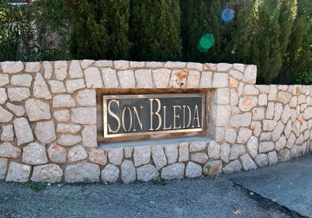 drystone: SOLLER MALLORCA SPAIN  FEBRUARY 7 2013: Entrance sign at the Son Bleda rural hotel with traditional drystone rocks black and gold sign on February 7 2013 in Soller Mallorca Spain.