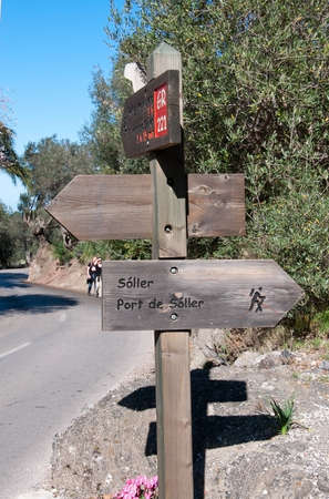drystone: SOLLER MALLORCA SPAIN  FEBRUARY 7 2013: Wood sign post by the Drystone route 221 and two walkers on February 7 2013 in Soller Mallorca Spain.