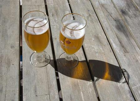 FALKENBERG SWEDEN  JUNE 5 2015: Two beers in Carlsberg logo glasses on rustic wooden table outdoors in sunshine on June 5 2015 in Falkenberg Sweden.