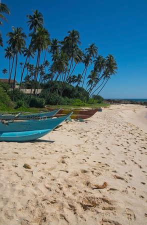 rocky point: Tangalle SRI LANKA 14 dicembre 2015: spiaggia con strette barche in legno chiaro turchese sulla spiaggia Rocky Point, il 14 dicembre 2015, Tangalle Sri Lanka.