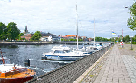 motorboats: HALMSTAD SWEDEN  JUNE 7 2015: Small motorboats moored along the quay by Nissan river with castle behind.