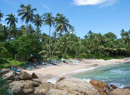 rocky point: TANGALLE SRI LANKA  DECEMBER 12 2015: Beach with small colorful light wood boats on the Rocky Point beach on December 12 2015 in Tangalle Sri Lanka.