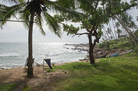 rocky point: TANGALLE SRI LANKA  DECEMBER 19 2015: Beach with lounge chair and wood boats on sandy beach in afternoon sun haze on the Rocky Point beach on December 19 2015 in Tangalle Sri Lanka.