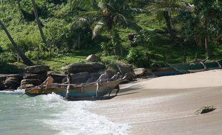 rocky point: Tangalle SRI LANKA 15 Dicembre 2015: Quattro uomini trascinare la loro piccola barca di legno fino sulla spiaggia di sabbia dopo un tour di pesca nel pomeriggio sulla spiaggia Rocky Point, il 15 dicembre 2015 a Tangalle Sri Lanka. Editoriali