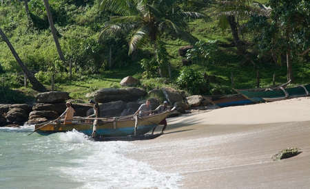 southern indian: TANGALLE SRI LANKA  DECEMBER 15 2015: Four men drag their small wooden boat up onto the sandy beach after a fishing tour in the afternoon on the Rocky Point beach on December 15 2015 in Tangalle Sri Lanka.