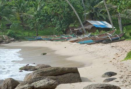 rocky point: Tangalle SRI LANKA 19 DICEMBRE 2015: spiaggia con le barche in legno chiaro turchese strette e vecchio capannone con tetto in lamiera ondulata sulla spiaggia Rocky Point, il 19 dicembre 2015 Tangalle Sri Lanka.