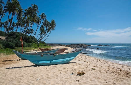 rocky point: TANGALLE SRI LANKA  DECEMBER 14 2015: Beach with narrow turquoise light wood boats on the Rocky Point beach on December 14 2015 in Tangalle Sri Lanka. Editorial
