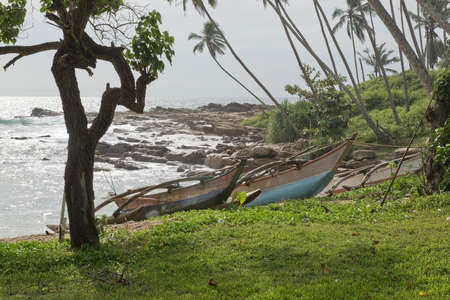 rocky point: Tangalle SRI LANKA 19 DICEMBRE 2015: spiaggia con le barche di legno sulla spiaggia di sabbia in sole di pomeriggio foschia sulla spiaggia Rocky Point il 19 dicembre 2015 Tangalle Sri Lanka.