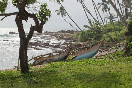 rocky point: TANGALLE SRI LANKA  DECEMBER 19 2015: Beach with wood boats on sandy beach in afternoon sun haze on the Rocky Point beach on December 19 2015 in Tangalle Sri Lanka. Editorial