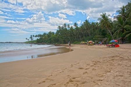 rocky point: Tangalle SRI LANKA 21 dicembre 2015: spiaggia con il surfista donna e ombrelloni sulla spiaggia sabbiosa al sole del pomeriggio foschia sulla spiaggia Rocky Point, il 21 dicembre 2015 Tangalle Sri Lanka.