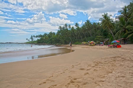 rocky point: TANGALLE SRI LANKA  DECEMBER 21 2015: Beach with surfer woman and parasols on sandy beach in afternoon sun haze on the Rocky Point beach on December 21 2015 in Tangalle Sri Lanka.