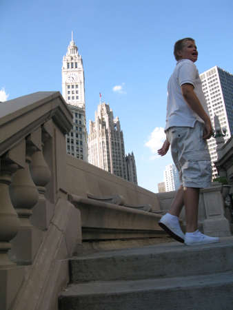 illinois river: CHICAGO, ILLINOIS, UNITED STATES - JULY 31, 2008: Boy walking upstairs from the river with Chicago buildings against blue sky on July 31, 2008 in Downtown Chicago, Illinois, United States.