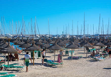 masts: CAN PASTILLA, MAJORCA - JULY 21, 2014: Life on the beach with parasols, sunlounge chairs and masts in the marina on a sunny summer day on July 21, 2014 in Can Pastilla, Mallorca, Spain. Editorial