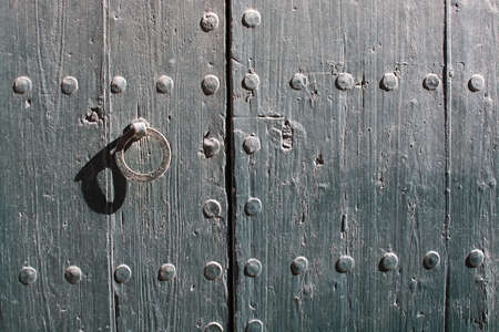 door lock: Wooden door with rusty iron lock background texture on a sunny day.