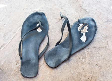 Flipflops torn distressed used and broken in black.